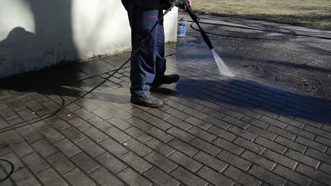 worker washes yard tiles Footage