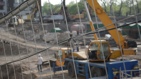 Fast construction site fence blur people work heavy equipment Footage