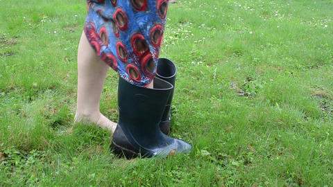 barefoot woman on meadow grass boot welly rubber shoes and walk Footage