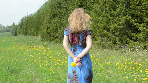 woman stand against hot summer wind hold dandelion flowers Footage