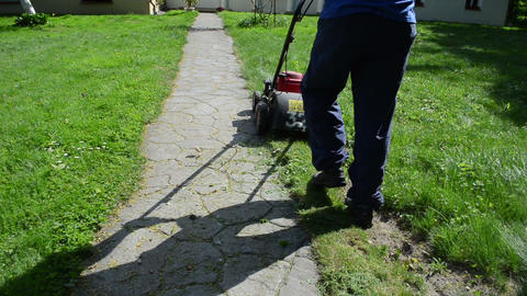 gardener man start grass lawn mower and cut grass stone path Live Action