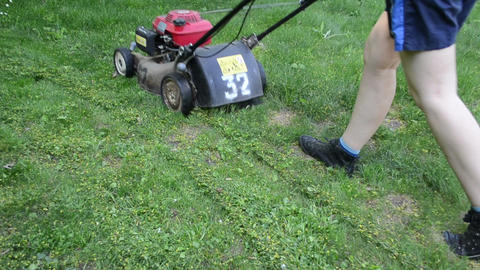 Walking woman cutting lawn with grass cutter mower on meadow Footage