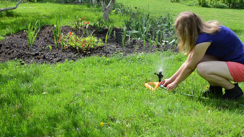 Gardener woman unplug hose to watering sprinkler equipment tool Live Action