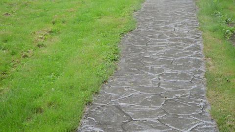 Strong lush rainfall fall on stone cobbly path between lawn Footage