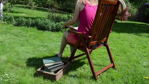 Woman in shorts sit on wooden chair and read study book Footage