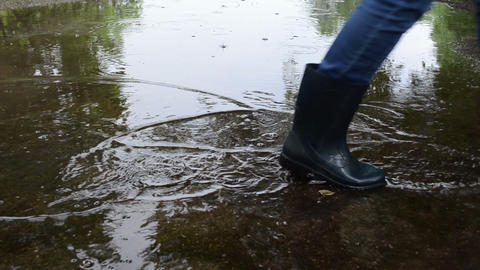 Air bubbles on poll soak water and woman in gumboots cross it Footage