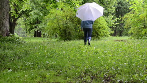 Woman with umbrella and gumboots walk between bushes and trees Footage