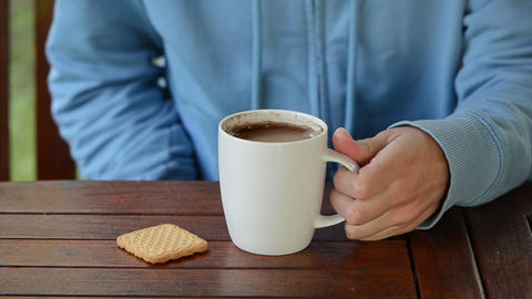 Hand take cup of steaming hot morning coffee and drink it Footage