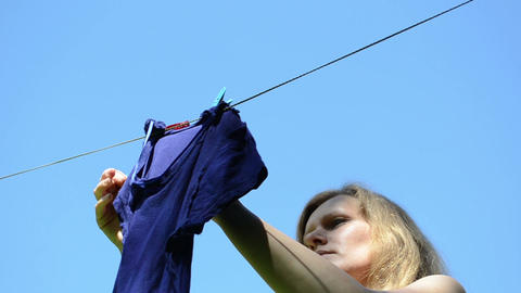 Woman hanging laundry on clothesline strings on sky background Footage