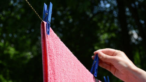 hand put pins clips on drying laundry hang on clothesline Footage