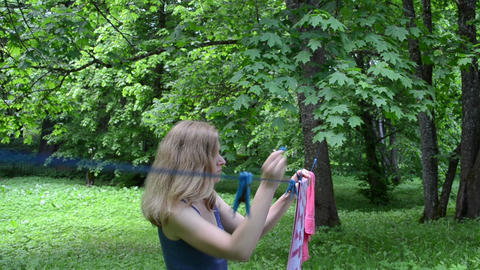woman hanging laundry towel on clothesline strings in garden Footage