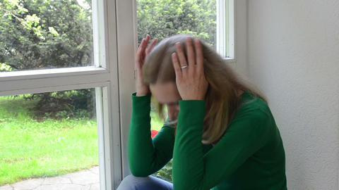 sad crouched woman sits on window sill Footage