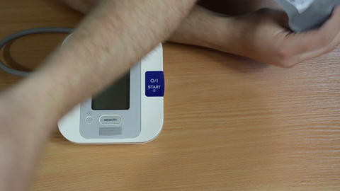 Hairy male patient put blood pressure measure tool on hand Footage