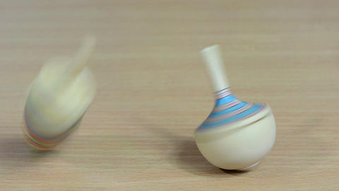 Hand try to spin whirligig peg-top toy on wooden background Footage
