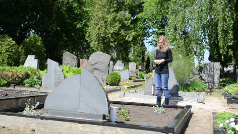 Sad woman cross pray near father husband grave in cemetery Footage