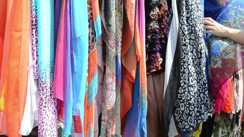 Hand choose multicolor cloaks shawls and scarves in market fair Footage