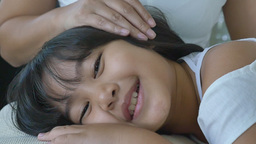 Happy little Asian girl sleep on her mother's lap Footage