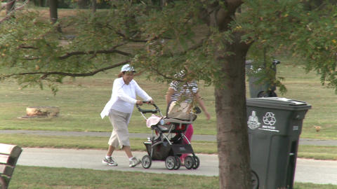 Two grandmothers pushing baby stroller in park Live Action