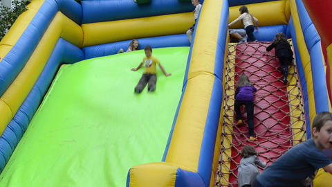 kids climb and slide on inflatable rubber castle playground Footage