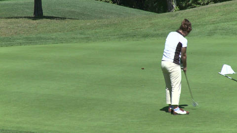 Female golfer putts ball and is excited (1 of 2) Footage