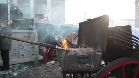 man bake meat chop firewood spring street fair fire smoke Footage