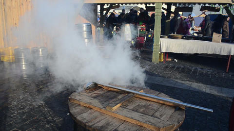 people buy hot drink wine boil huge pots smoke rise fair market Footage
