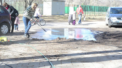 girl with a strong jet of water cleans the asphalt Stock Video Footage