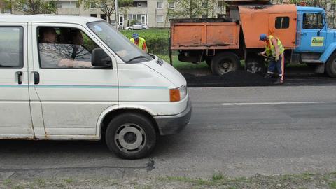 workers shovel put hot asphalt street road holes street repair Footage