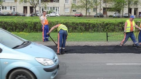 workers shovels put hot asphalt street road holes street repair Footage