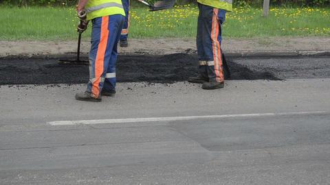 workers put hot asphalt street holes heavy vibration roller Stock Video Footage