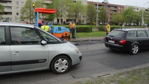 men work heavy asphalt road repair roller passing cars in... Stock Video Footage