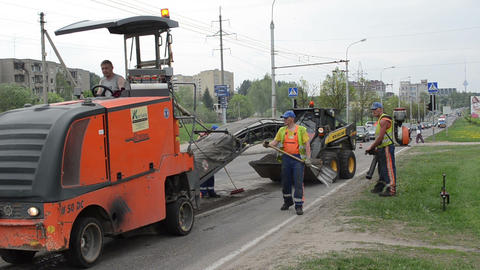 Cold planer machine mill asphalt workers work on traffic street Footage
