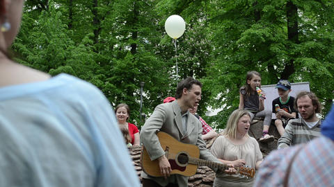 People play guitar and sing songs for kids in free city event Footage