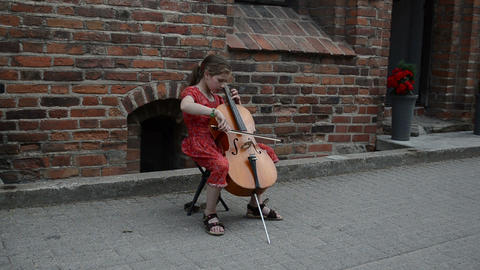 Young girl play with cello violoncello old town street music day Footage