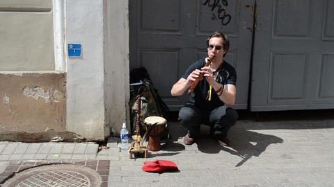 Man play with flute pipe in old town street event Footage