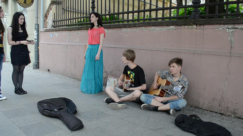 young guitarists play guitar and girl in long skirt sing Footage