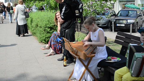 girl play string instrument and people in street Stock Video Footage