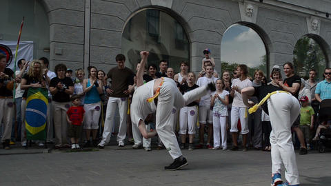 Man and woman perform capoeira dance in center of singing people Footage