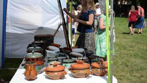 crockery pots hand craft sold in outdoor market fair and people Footage