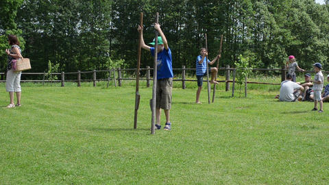 Kids try to walk on stilts in rural village homestead Footage