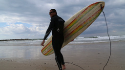 Surfer on the beach enter the water Stock Video Footage