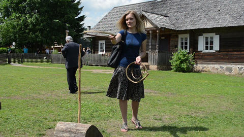 Woman girl in skirt play throw wooden rings on stick in... Stock Video Footage