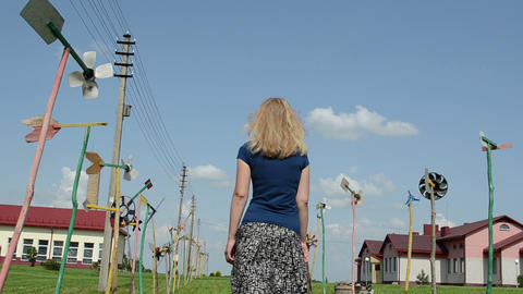 girl with skirt go between spin toy pinwheel windmills... Stock Video Footage