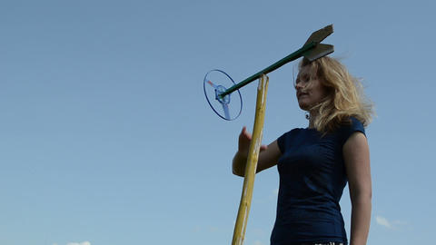 beautiful woman play with spin windmill pinwheel toy on blue sky Footage