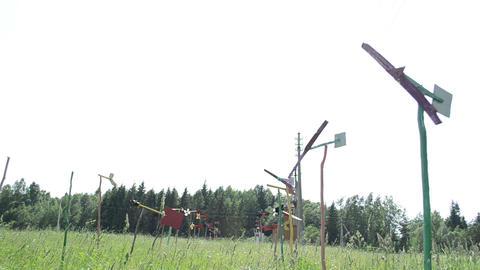 pinwheel windmills collection set spin between high grass Stock Video Footage