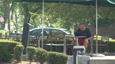 Person sitting at a table along sidewalk Stock Video Footage
