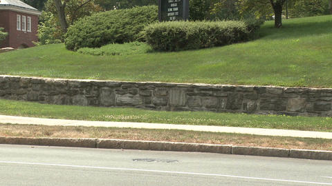 Bike riding down sidewalk with stone wall along side of it Stock Video Footage