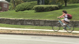 Bike riding down sidewalk with stone wall along side of it Footage