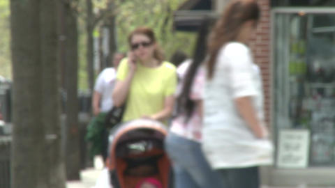 Mother walking down sidewalk with stroller talking on the... Stock Video Footage