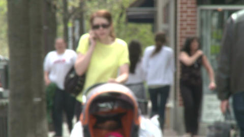 Mother walking down sidewalk with stroller talking on the phone Footage